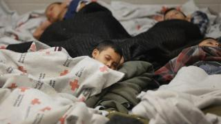 children sleeping in a holding cell